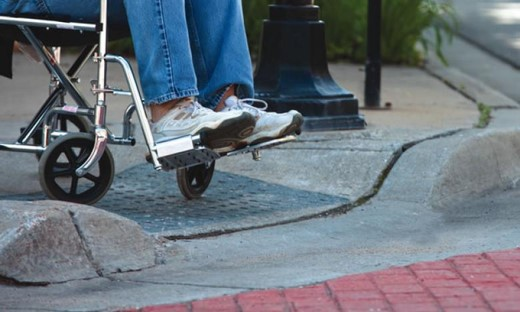 Someone sitting in a wheel chair using a curb cut